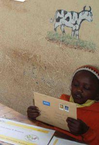 Harun Waweru Kamau begutachtet neugierig den Patenbrief seiner Pateneltern Beatrix und Uwe.